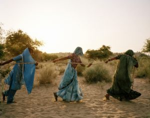 Title: Pulling of the well, Tharpakar, Pakistan, 2013. Caption: Women of Tharpakar in the southern Sindh Province of Pakistan work together to pull water from a well. Even when one person is done, they all remain at the well to share in the task. One of the effects of the flooding was salinity in the ground, which affected the ability for the agricultural region to support itself. The water gathered is brackish and dangerous to the health of children, who often suffer diarrhea and other water-borne illnesses. Tharpakar, Pakistan, 2013.