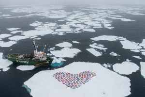 The crew of the Greenpeace ship MY Arctic Sunrise construct a 'heart' with the flags of the 193 country members of the United Nations on an ice floe north of the Arctic Circle. The 'heart' of flags is suspended by wires a few centimetres from the ice surface and symbolizes an emotional appeal for united global action to protect the Arctic. Greenpeace International is hosting an event in New York on the eve of the UN General Assembly which will present the latest science on changes in the Polar regions and then discuss an appropriate response from the international community. Scientists from the National Snow and Ice Data Center (NSIDC) release preliminary figures suggesting that Arctic sea ice has reached the lowest recorded extent since records began in 1979. The data indicates that on September 16th Arctic ice extent covered 3.41 m km2 - a drop of at least 45% since records began.